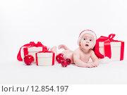 Маленькая девочка в красном колпаке лежит на полу с новогодними игрушками и подарками. Стоковое фото, фотограф Иван Траймак / Фотобанк Лори