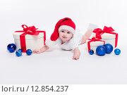 Милый ребенок лежит на животе среди елочных игрушек и подарочных коробок. Стоковое фото, фотограф Иван Траймак / Фотобанк Лори