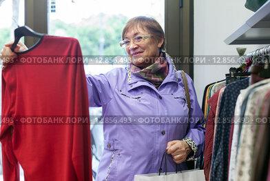 Женщина выбирает одежду в магазине