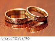 Купить «Два золотых обручальных кольца лежат на столе», эксклюзивное фото № 12859165, снято 1 августа 2015 г. (c) Игорь Низов / Фотобанк Лори