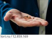 Купить «Золотые обручальные кольца в фокусе лежат на ладони жениха», эксклюзивное фото № 12859169, снято 1 августа 2015 г. (c) Игорь Низов / Фотобанк Лори