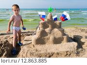 Купить «Мальчик строит большой замок из песка на пляже», эксклюзивное фото № 12863885, снято 24 сентября 2015 г. (c) Алексей Бок / Фотобанк Лори