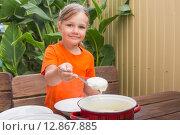 Купить «Девочка с улыбкой накладывает манную кашу себе в тарелку», фото № 12867885, снято 22 сентября 2015 г. (c) Иванов Алексей / Фотобанк Лори