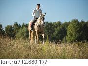 Купить «Молодой мужчина верхом на лошади», фото № 12880177, снято 4 октября 2015 г. (c) Andriy Bezuglov / Фотобанк Лори