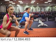 Купить «Fit couple working out in weights room», фото № 12884493, снято 16 июля 2015 г. (c) Wavebreak Media / Фотобанк Лори