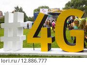 Купить «Рекламная конструкция с названием высокоскоростной сети Интернет 4G в парке города Москвы во время праздника красок Холи, Россия», фото № 12886777, снято 12 июля 2015 г. (c) Николай Винокуров / Фотобанк Лори