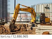 Купить «Экскаватор проводит земельные работы на территории завода Лукойл», фото № 12886965, снято 16 октября 2015 г. (c) Сергей Сергеев / Фотобанк Лори