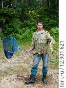 Купить «Счастливый рыбак с большим лещём и сачком в руках стоит на берегу», эксклюзивное фото № 12901621, снято 2 июля 2015 г. (c) Игорь Низов / Фотобанк Лори
