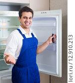 Купить «Handyman repairing refrigerator in kitchen», фото № 12910213, снято 30 марта 2020 г. (c) Яков Филимонов / Фотобанк Лори