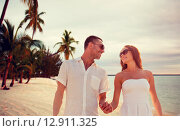 Купить «smiling couple in sunglasses walking on beach», фото № 12911325, снято 23 июля 2014 г. (c) Syda Productions / Фотобанк Лори