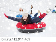 Купить «group of happy friends sliding down on snow tubes», фото № 12911469, снято 19 января 2015 г. (c) Syda Productions / Фотобанк Лори