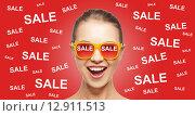 Купить «happy teenage girl in shades with sale signs», фото № 12911513, снято 27 января 2020 г. (c) Syda Productions / Фотобанк Лори