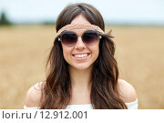 Купить «smiling young hippie woman in sunglasses outdoors», фото № 12912001, снято 27 августа 2015 г. (c) Syda Productions / Фотобанк Лори