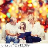 Купить «happy family with book at home», фото № 12912389, снято 1 марта 2014 г. (c) Syda Productions / Фотобанк Лори