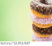 Купить «close up of glazed donuts pile over green», фото № 12912937, снято 21 мая 2015 г. (c) Syda Productions / Фотобанк Лори