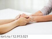 close up of senior and young woman holding hands. Стоковое фото, фотограф Syda Productions / Фотобанк Лори