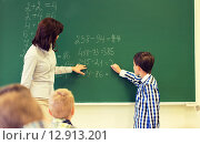 Купить «schoolboy with math teacher writing on chalk board», фото № 12913201, снято 15 ноября 2014 г. (c) Syda Productions / Фотобанк Лори
