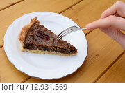 Woman uses dessert fork to cut into a slice of pecan pie. Стоковое фото, фотограф Sarah Marchant / PantherMedia / Фотобанк Лори
