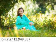 Купить «Девушка в длинном платье сидит на траве в лесу в солнечную погоду», фото № 12949357, снято 27 августа 2015 г. (c) Иванов Алексей / Фотобанк Лори