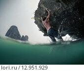 Купить «Мужчина держится за скалу нависая над морем», фото № 12951929, снято 21 марта 2015 г. (c) Михаил Дударев / Фотобанк Лори