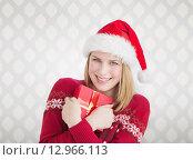 Купить «Composite image of woman holding christmas present», фото № 12966113, снято 19 февраля 2019 г. (c) Wavebreak Media / Фотобанк Лори