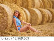 Купить «Ферма. Девушка сидит на фоне катушек сена», фото № 12969509, снято 16 августа 2015 г. (c) Литвяк Игорь / Фотобанк Лори