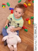 Купить «Маленький ребенок играет с игрушками», фото № 12984277, снято 27 октября 2015 г. (c) Виктор Топорков / Фотобанк Лори