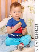 Купить «Маленький ребенок сидит в кроватке», фото № 12984285, снято 26 октября 2015 г. (c) Виктор Топорков / Фотобанк Лори