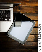 Купить «Ноутбук, цифровой планшет и мобильный телефон на столе», фото № 12997309, снято 14 октября 2015 г. (c) Валерия Потапова / Фотобанк Лори