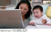 Купить «Mother with crying baby using laptop », видеоролик № 13000321, снято 10 апреля 2020 г. (c) Wavebreak Media / Фотобанк Лори