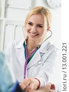 Веселая девушка в белом медицинском халате измеряет давление пациенту. Стоковое фото, фотограф Людмила Дутко / Фотобанк Лори