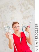 Розетка и рабочие инструменты в руках удивленной молодой женщины. Стоковое фото, фотограф Petri Jauhiainen / Фотобанк Лори