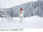 Женщина в вязаной красной шапке и свитере катается на лыжах в лесу. Стоковое фото, фотограф Petri Jauhiainen / Фотобанк Лори