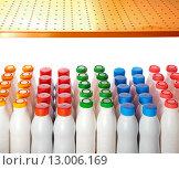 Купить «Молочные продукты в бутылках с разноцветными крышками стоят на полке магазина», фото № 13006169, снято 9 мая 2012 г. (c) Куликов Константин / Фотобанк Лори