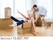 Купить «couple with cardboard boxes having fun at new home», фото № 13007797, снято 6 июня 2015 г. (c) Syda Productions / Фотобанк Лори