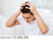Купить «unhappy man suffering from head ache at home», фото № 13008285, снято 29 января 2015 г. (c) Syda Productions / Фотобанк Лори
