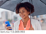 Купить «businesswoman with umbrella texting on smartphone», фото № 13009993, снято 8 июля 2015 г. (c) Syda Productions / Фотобанк Лори