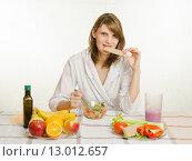Купить «Молодая девушка кусает хлебец, закусывая им вегетарианский овощной салат», фото № 13012657, снято 14 февраля 2015 г. (c) Иванов Алексей / Фотобанк Лори