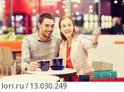 Купить «happy couple with shopping bags drinking coffee», фото № 13030249, снято 10 ноября 2014 г. (c) Syda Productions / Фотобанк Лори