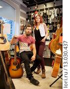Купить «couple of musicians with guitar at music store», фото № 13030437, снято 11 декабря 2014 г. (c) Syda Productions / Фотобанк Лори