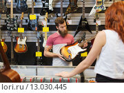 Купить «assistant showing customer guitar at music store», фото № 13030445, снято 11 декабря 2014 г. (c) Syda Productions / Фотобанк Лори
