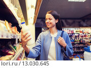 Купить «happy woman holding milk bottle in market», фото № 13030645, снято 20 декабря 2014 г. (c) Syda Productions / Фотобанк Лори