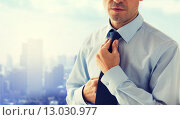 Купить «close up of man in shirt adjusting tie on neck», фото № 13030977, снято 13 ноября 2014 г. (c) Syda Productions / Фотобанк Лори