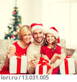 Купить «smiling family holding gift boxes and sparkles», фото № 13031005, снято 26 октября 2013 г. (c) Syda Productions / Фотобанк Лори