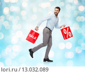 Купить «smiling man with red shopping bag», фото № 13032089, снято 3 октября 2015 г. (c) Syda Productions / Фотобанк Лори