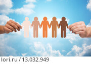 hands holding chain of people pictogram over sky. Стоковое фото, фотограф Syda Productions / Фотобанк Лори