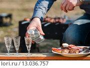 Купить «Мужчина разливает водку в рюмки на фоне шашлыка», эксклюзивное фото № 13036757, снято 12 апреля 2015 г. (c) Игорь Низов / Фотобанк Лори