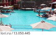 Пляжные зонты и лежаки у главного бассейна. Территория отеля Alf Leila Wa Leila (1001 Nights, сеть Альбатрос). Хургада, Египет (2015 год). Редакционное видео, видеограф Кекяляйнен Андрей / Фотобанк Лори