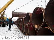 Склад труб большого диаметра на улице зимой. Рабочие грузят продукцию. Санкт-Петербург (2015 год). Редакционное фото, фотограф Игорь Акимов / Фотобанк Лори