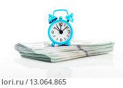 Купить «Время - деньги. Будильник и доллары на белом фоне», фото № 13064865, снято 2 апреля 2015 г. (c) Валерия Потапова / Фотобанк Лори